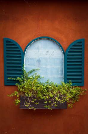 Open Window With Flower Basket On Orange Wall Stock Photo