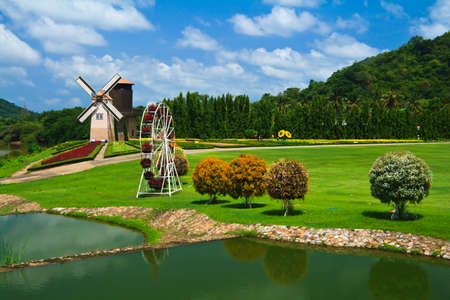 Colorful Garden With Romantic Windmill Behind a Lake And Blue Sky Stock Photo - 13809295