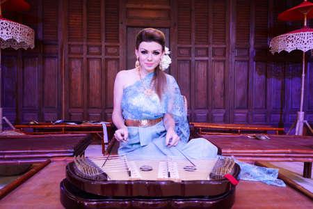 thai musical instrument: European Woman Dress In Thailand National Costume And Playing Thai Musical Instrument Dulcimer