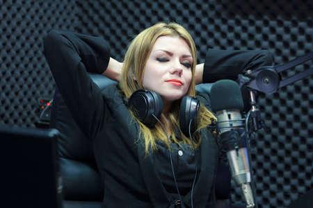 mujer descansando: Feliz �xito hermosa de DJ reclinaci�n de la mujer mientras trabajaba en Recording Studio Sala
