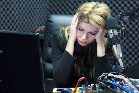 Beautiful Woman Serious And Moody While Working As DJ Radio Live Show In Studio photo