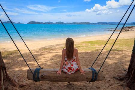 Woman Sitting On Log Swing On The Beach photo