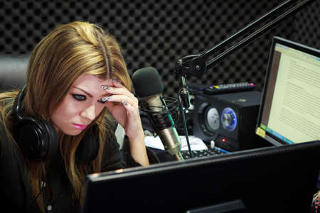 Woman Serious And Moody While Working As DJ Radio Live Show In Studio photo