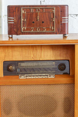 winder: Vintage Winder Table Clock And Very Old Music Juke Box Stock Photo