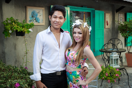 interracial love: Interracial Love Couple Handsome Asian Man And Pretty Caucasian Woman Hugging And Posing In The Garden