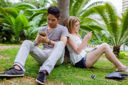 interracial couple: Interracial Couple Lovers Sitting On The Grass With Mobile In Their Hands Stock Photo