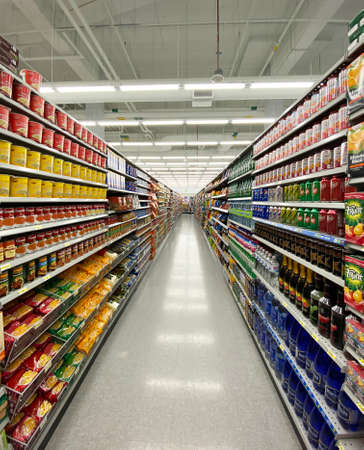 Photography of a generic supermarket aisle or grocery store aisle showing shelves filled with products. Can be used as background for marketing and retail branding. Banque d'images