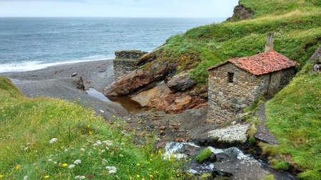 Old mill next to the waterfall on 'La Vallina' beach, Ovi ana, Cudillero, Asturias, Spain