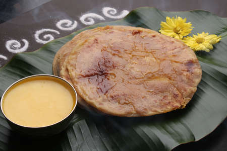 Puran Poli, also known as Holige, is an Indian sweet flatbread from India consumed mostly during Holi festival. Served on banana leaf with pure Ghee over black background.