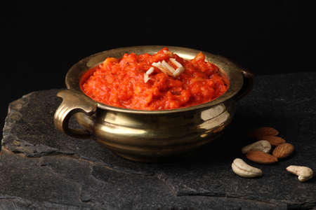 Gajar ka halwa is a carrot-based sweet dessert pudding from India. Garnished with Cashew almond nuts and Served in bowl.