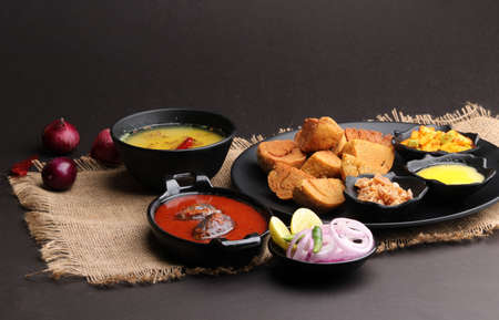 bafle or bati is popular main course dish in India served with dal daal brinjal curry jaggery gud and clarified butter or ghee
