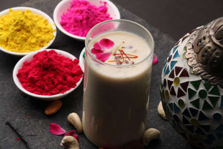 Indian festival Holi concept - Traditional Indian beverage Thandai Sardai milk festival food, with nuts and color in bowl.
