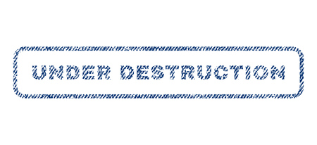 quake: Under Destruction text textile seal stamp watermark. Blue jeans fabric rasterized texture. Raster tag inside rounded rectangular shape. Rubber sign with fiber textile structure.