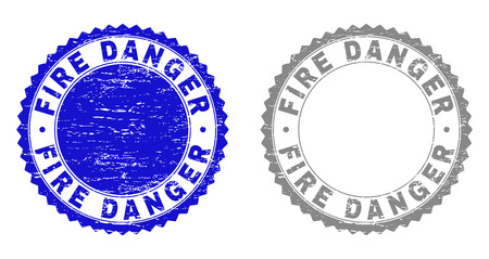 Grunge FIRE DANGER stamp seals isolated on a white background. Rosette seals with distress texture in blue and gray colors. Vector rubber stamp imitation of FIRE DANGER caption inside round rosette.