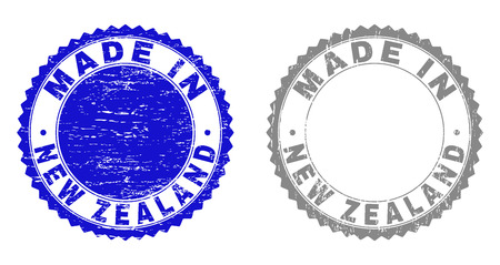 Grunge MADE IN NEW ZEALAND stamp seals isolated on a white background. Rosette seals with distress texture in blue and grey colors. Çizim