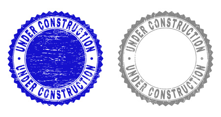 Grunge UNDER CONSTRUCTION stamp seals isolated on a white background. Rosette seals with grunge texture in blue and gray colors. Vector rubber overlay of UNDER CONSTRUCTION label inside round rosette.