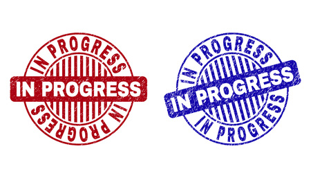 Grunge IN PROGRESS round stamp seals isolated on a white background. Round seals with grunge texture in red and blue colors.