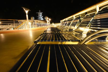 Evening lounge chairs in a row on a ocean cruise ship promenade deck  Stock Photo