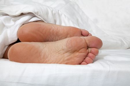 laziness: Feet in bed Stock Photo