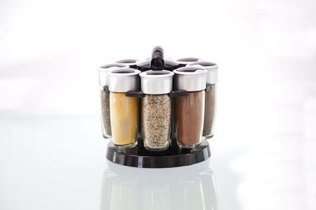 spice: Cruet-stand with spice jars on white background.