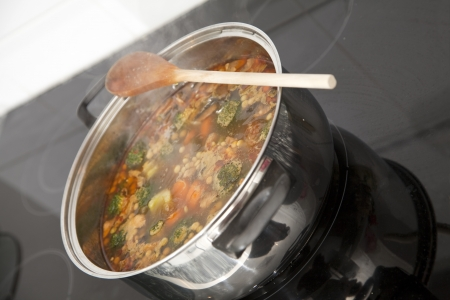 Boiling pot of soup on top of the stove. Focus across the middle of image.
