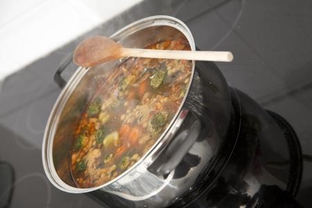 Kokend pot soep op de top van de kachel. Richten zich in het midden van de afbeelding.