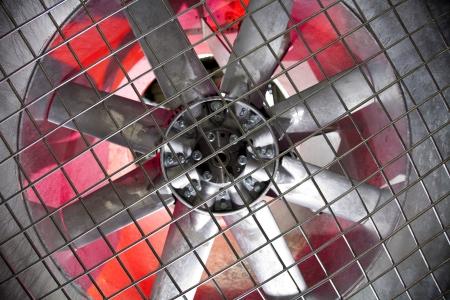 Industrial fan behind a metal grate,