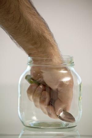 Hand in pot met een lepel