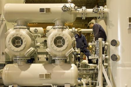 compresor: Estación de compresión de gas natural con dos técnicos que trabajan