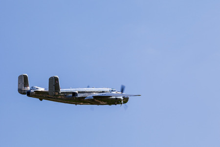 monoplane: BUDAPEST, HUNGARY - MAY 1: B-25 Mitchell historic bomber plane fly-by with Red Bull marking on it