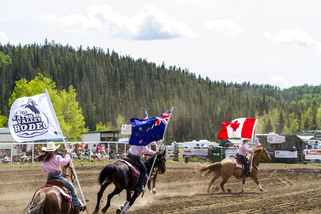 a rural community: WATER VALLEY, CANADA - JUN 6 2015: Unidentified flag bearers opens the Bucking Horse Competition in Water Valley. This annual event is important in the rural as well as the sport loving community. Editorial