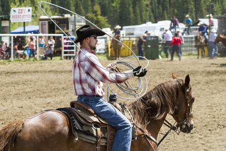 arena rodeo: WATER VALLEY CANADA  JUN 6 2015:Unidentified Cowboy participating in the  Lasso event Water Valley Rodeo.This annual event is important for the rural as well as the sport loving community. Editorial