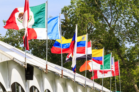 snob: CALGARY CANADA - JUN 7 2015   National Flags  in action during the prestige s Spruce Meadows International hors jumping competition,  riders comes all over the world to compete.