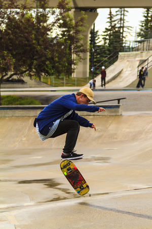 CALGARY, CANADA - JUN 21, 2015: Athletes have a friendly skateboard competition in Calgary. California law requires anyone under the age of 18 to wear a helmet while riding a skateboard. Stock fotó - 45771047