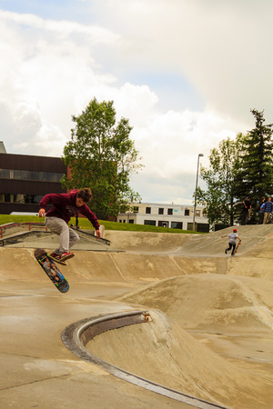 CALGARY, CANADA - JUN 21, 2015: Athletes have a friendly skateboard competition in Calgary. California law requires anyone under the age of 18 to wear a helmet while riding a skateboard. Stock fotó - 45771109