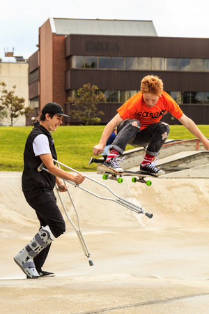 friendly competition: CALGARY, CANADA - JUN 21, 2015: Athletes have a friendly skateboard competition in Calgary. California law requires anyone under the age of 18 to wear a helmet while riding a skateboard.
