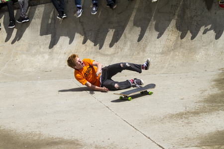 requires: CALGARY, CANADA - JUN 21, 2015: Athletes have a friendly skateboard competition in Calgary. California law requires anyone under the age of 18 to wear a helmet while riding a skateboard.