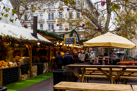 each year: BUDAPEST, HUNGARY - DEC 19 2015: Tourists enjoy the Christmas market in the city center on in Budapest, Hungary. This traditional Christmas fair attracts 700,000 visitors each year.