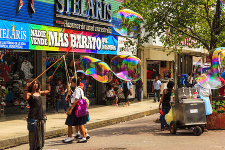contributes: PANAMA CITY, PANAMA: OCT. 24 2015: Pedestrians watch an amazing soap bubble performer in the down town of Panama City. Performers contributes to the colorful scape of the city. Editorial