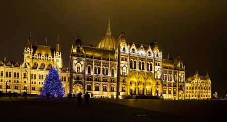 each year: BUDAPEST, HUNGARY - DEC 19 2015: Tourists enjoy the Christmas lights at the Parliament House in Budapest, Hungary. This traditional Christmas fair attracts abut 700,000 visitors each year.