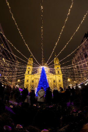 each year: BUDAPEST, HUNGARY - DEC 19 2015: Tourists enjoy the Christmas lights at the St Steven Basilica in Budapest, Hungary. This traditional Christmas fair attracts abut 700,000 visitors each year.