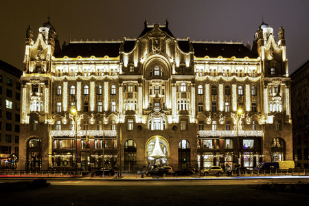 each year: BUDAPEST, HUNGARY - DEC 19 2015: Gresham Palace at night with Christmas lights at the in Budapest, Hungary. This traditional Christmas fair attracts abut 700,000 visitors each year.