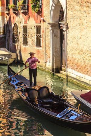 Gondoliere auf einer Gondel auf dem Canal Grande nehmen Touristen für eine Fahrt. Venedig. Gondel sind ein wichtiger Modus der touristische Verkehr in Venedig, Italien.