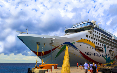 embark: COZUMEL, MEXICO - JAN 26 2016: NCL Dawn at Cozumel port. Over 3,500 passengers visited that beautiful tropical island. The economy of Cozumel is based on tourism.