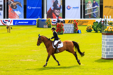 CALGARY CANADA - JUN 7 2015 :  Spruce Meadows International hors jumping competition, — Stock Photo #77782566 CALGARY CANADA - JUN 7 2015 Unidentified rider in action during the prestige s Spruce Meadows International hors jumping competition, riders co