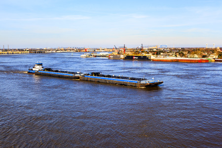 NEW ORLEANS USA 25.JAN. 2016: Un remorqueur pousse une péniche dans le fleuve Mississippi à la Nouvelle-Orléans. C'est une pratique courante de déplacer des objets lourds et en vrac. Banque d'images - 59371143