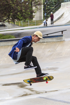 show off: CALGARY, CANADA - JUN 21, 2015: Athletes have a friendly skateboard Show Off in Calgary. California law requires anyone under the age of 18 to wear a helmet while riding a skateboard.