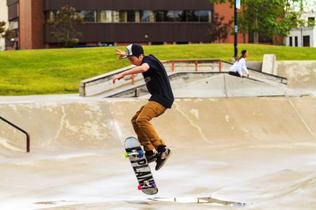 requires: CALGARY, CANADA - JUN 21, 2015: Athletes have a friendly skateboard Show Off in Calgary. California law requires anyone under the age of 18 to wear a helmet while riding a skateboard.