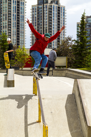 skate park: CALGARY, CANADA - JUN 21, 2015: Athletes have a friendly skateboard Show Off in Calgary. California law requires anyone under the age of 18 to wear a helmet while riding a skateboard.