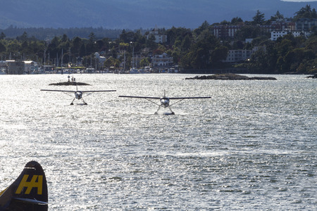 :   VICTORIA, BC, CANADA - JULY 26 2016: Harbor Air Float-plane in the inner harbor. This transportation is vital and very frequent between Vitoria and Vancouver, also the flight is very pictures.